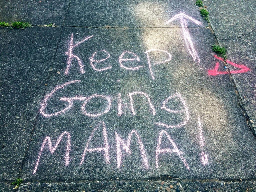 "Chalk written on the pavement, reading ""Keep going Mama!"""